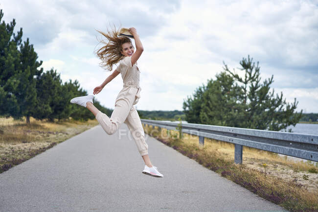 Cheerful woman jumping on rural road — Stock Photo