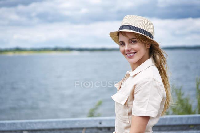 Porträt einer lächelnden Frau mit Hut am Seeufer — Stockfoto