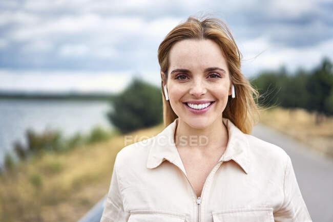 Retrato de mulher sorridente com fones de ouvido sem fio na natureza — Fotografia de Stock
