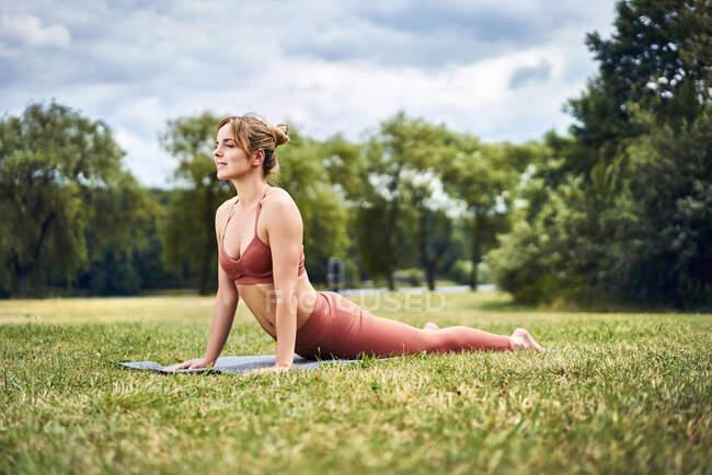 Женщина, занимающаяся позой кобры во время занятий йогой в парке — стоковое фото