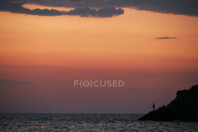 Silhueta de pessoa que pesca no mar ao nascer do sol — Fotografia de Stock