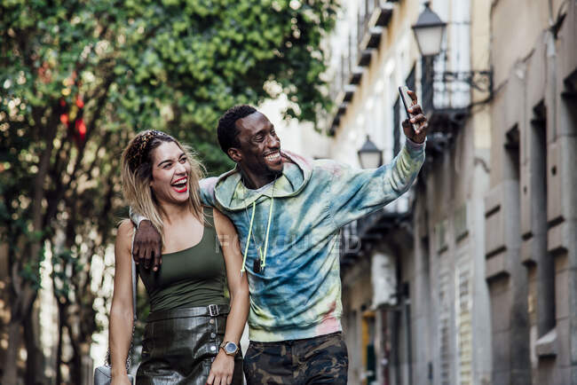 Retrato de pareja riendo tomando selfie con smartphone, Madrid, España - foto de stock