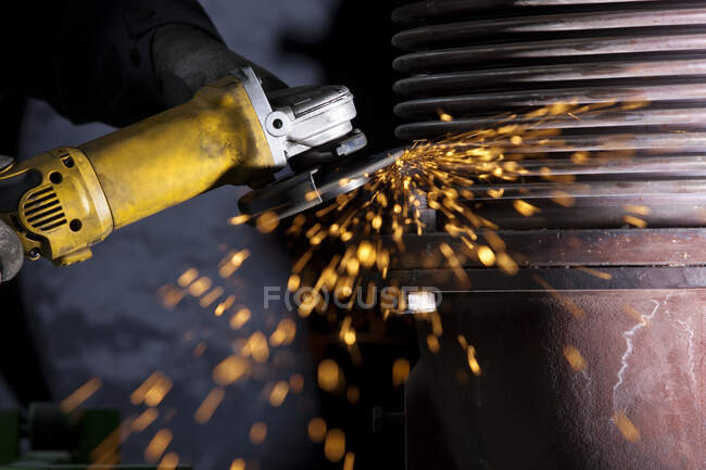 Close-up of worker using angle grinder in a factory — Stock Photo