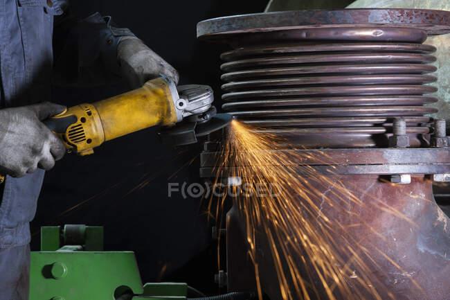 Nahaufnahme eines Arbeiters mit einem Winkelschleifer in einer Fabrik — Stockfoto