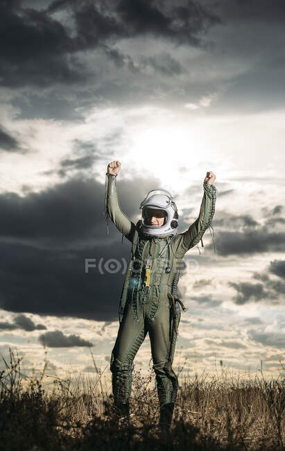 Man posing dressed as an astronaut on a meadow with dramatic clouds in the background — Stock Photo