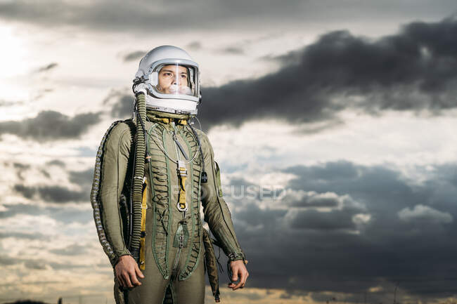 Man posing dressed as an astronaut with dramatic clouds in the background — Stock Photo