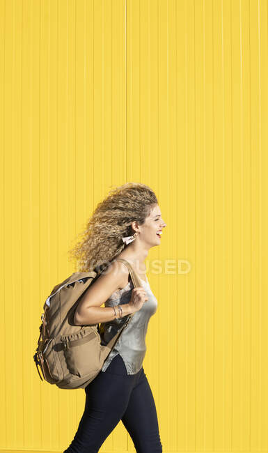 Молода жінка несе рюкзак перед жовтим фоном. — стокове фото