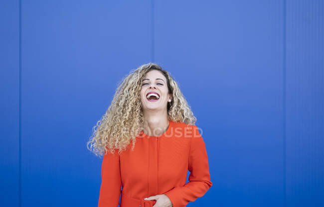 Portrait of laughing young woman wearing red dress in front of blue background — Stock Photo