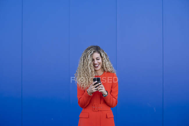 Portrait of young woman wearing red dress using cell phone in front of blue background — Stock Photo