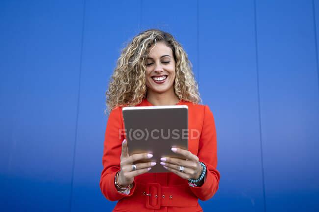 Retrato de una joven vestida de rojo delante de un fondo azul usando una tableta digital - foto de stock