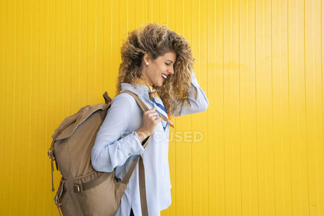 Laughing young woman carrying backpack in front of yellow background — Stock Photo