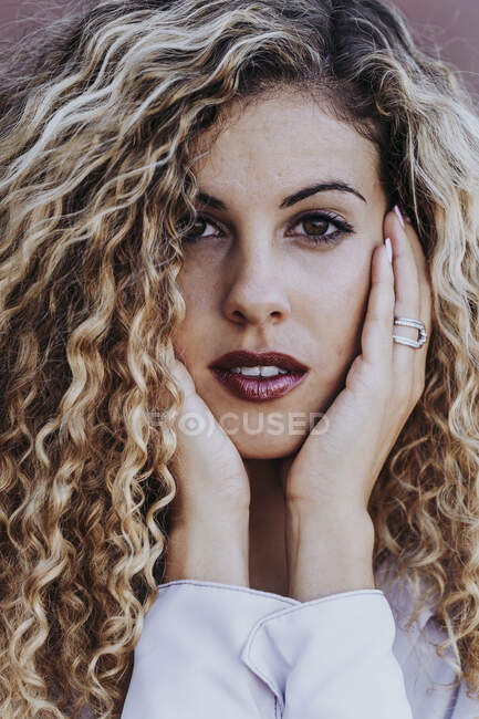 Portrait of young woman with dyed blond ringlets — Stock Photo