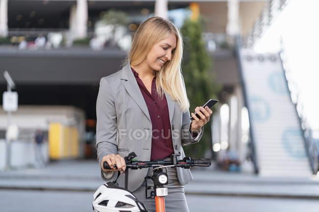 Усміхнена комерсантка з електричним скутером дивиться на мобільний телефон. — стокове фото
