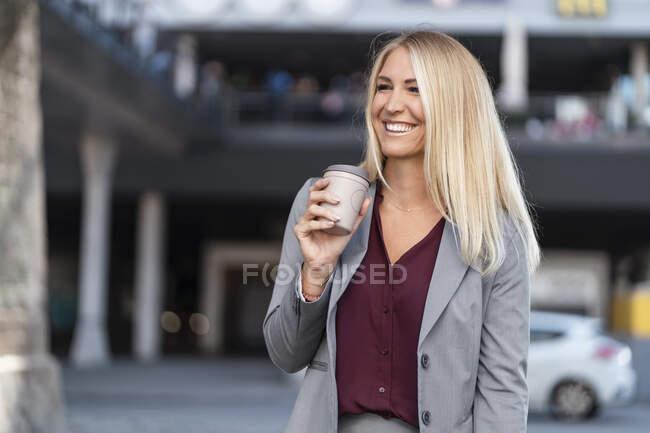 Portrait of happy blond businesswoman with coffee to go — Stock Photo