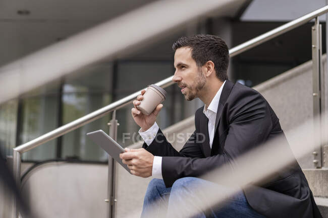 Businessman with tablet and takeaway coffee sitting on stairs in the city — Stock Photo