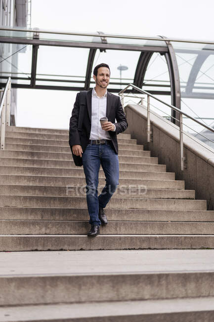 Businessman with takeaway coffee walking on stairs in the city — Stock Photo