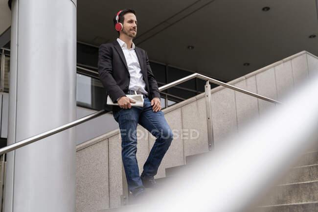 Empresário com fones de ouvido em pé nas escadas da cidade — Fotografia de Stock