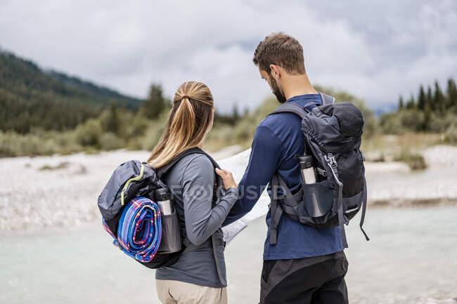 Молодая пара в походе читать карту, Vorderriss, Бавария, Германия — стоковое фото