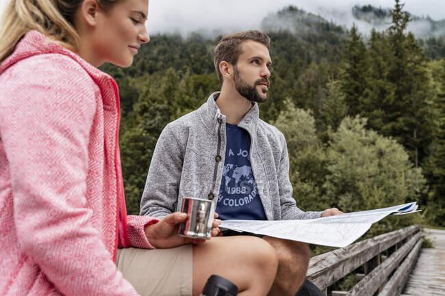 Parejas jóvenes en un viaje de senderismo con bebida y mapa, Vorderriss, Bavaria, Alemania - foto de stock