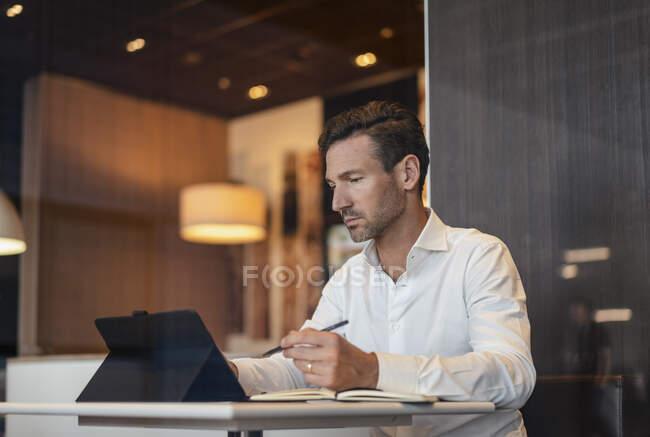 Бізнесмен користується планшетом і записує в кафе. — стокове фото
