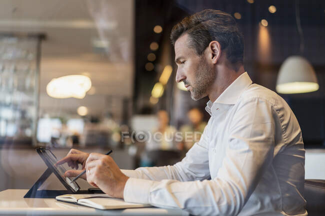 Businessman using tablet and taking notes in a cafe — Stock Photo