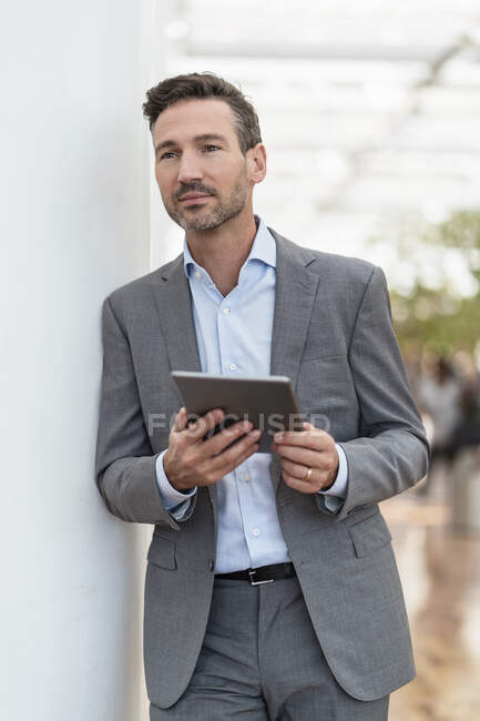 Businessman with tablet in the city — Stock Photo