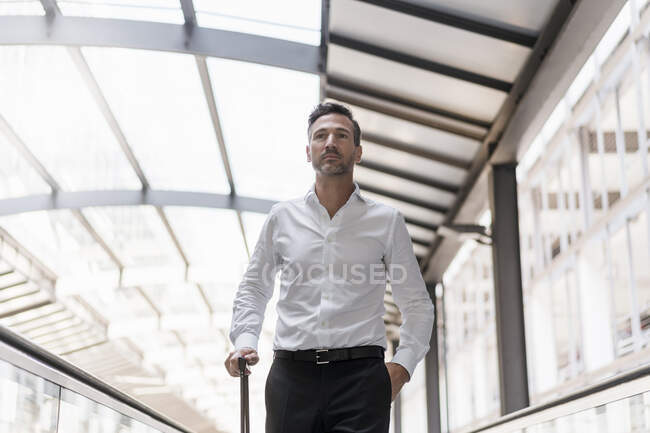 Businessman on moving walkway at the airport — Stock Photo