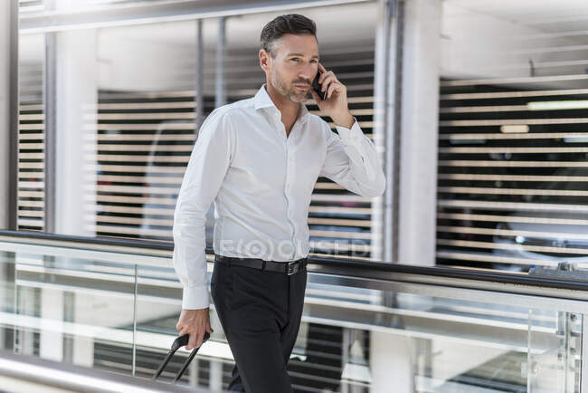 Businessman on escalator talking on the phone — Stock Photo