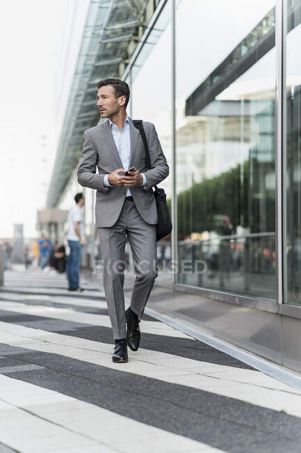 Portrait of businessman with cell phone on the go — Stock Photo