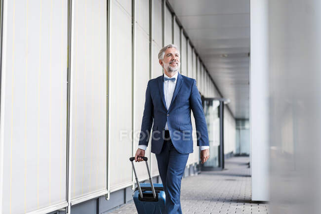 Mature businessman in a passageway with rolling suitcase on the go — Stock Photo