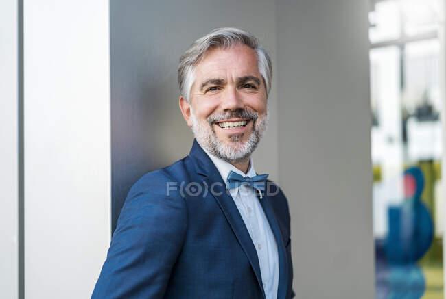 Retrato de sonriente elegante hombre de negocios maduro al aire libre - foto de stock