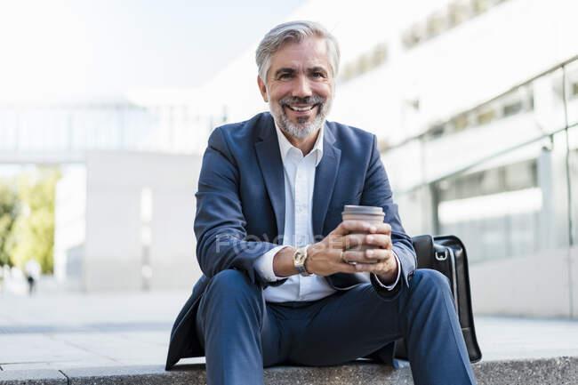 Портрет дорослого бізнесмена, який сидить на сходах у місті і забирає каву. — стокове фото