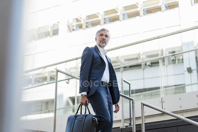 Mature businessman holding bag walking down stairs in the city — Stock Photo