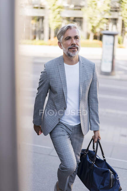 Fashionable mature businessman with travelling bag on the go in the city — Stock Photo