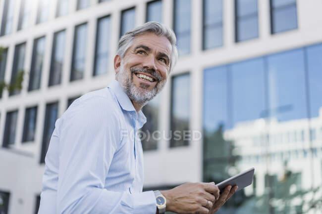 Sonriente hombre de negocios maduro utilizando tableta en la ciudad - foto de stock