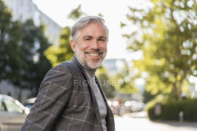 Портрет усміхненого дорослого бізнесмена в місті. — стокове фото