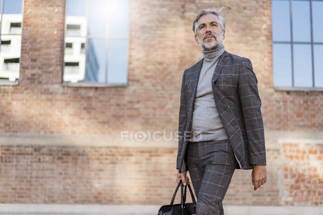 Fashionable mature businessman with bag on the go in the city — Stock Photo