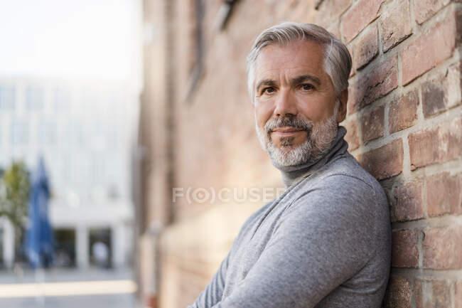 Retrato del hombre de negocios maduro apoyado en una pared de ladrillo - foto de stock