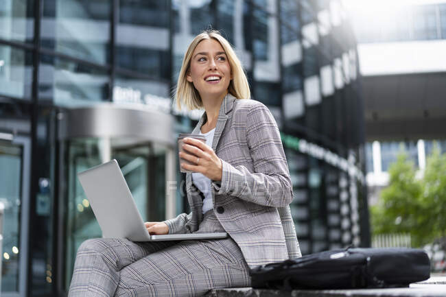 Smiling young businesswoman using laptop in the city — Stock Photo