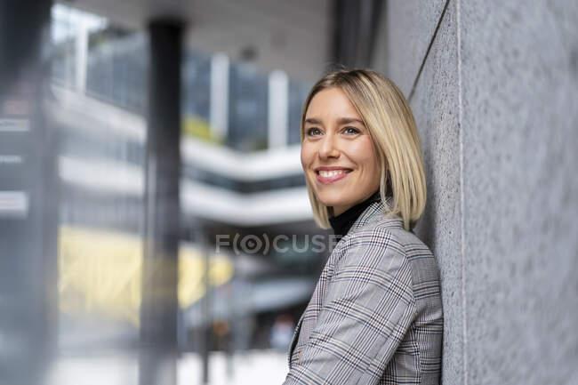 Portrait d'une jeune femme d'affaires souriante appuyée contre un mur — Photo de stock