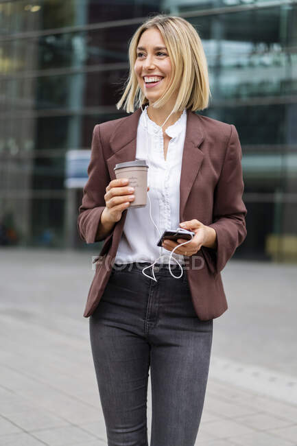 Happy young businesswoman in the city on the go — Stock Photo