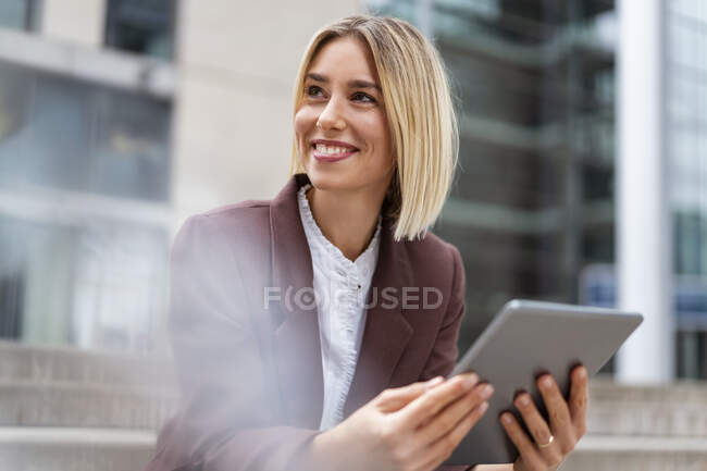 Smiling young businesswoman using tablet in the city — Stock Photo