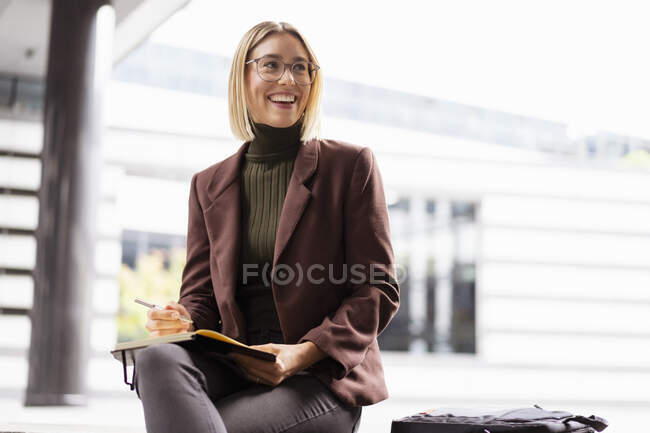 Smiling young businesswoman with notebook in the city — Stock Photo