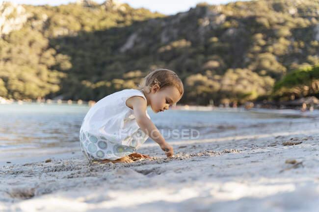Menina bonito da criança brincando na praia — Fotografia de Stock