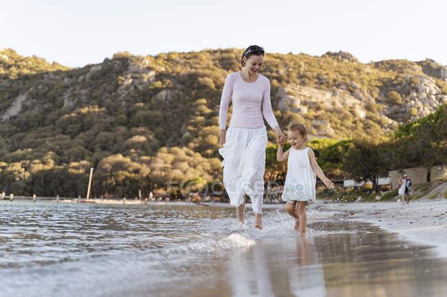 Mãe feliz com a filha andando à beira-mar — Fotografia de Stock