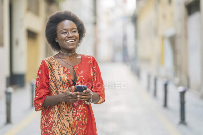 Laughing young woman standing with her smartphone in the middle of  a street — Stock Photo