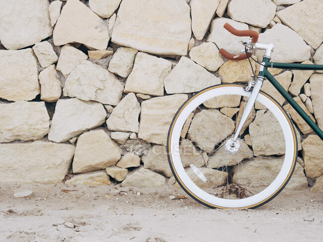 Fixie bike leaning against natural stone wall, partial view — Stock Photo