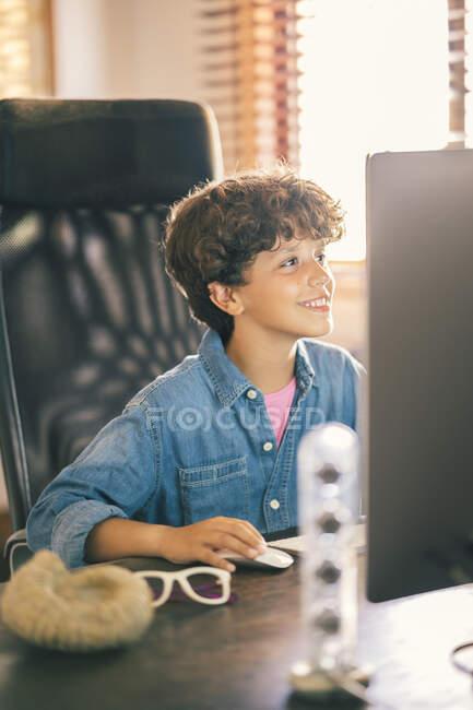 Niño sonriente sentado en el escritorio en casa usando un ordenador personal - foto de stock