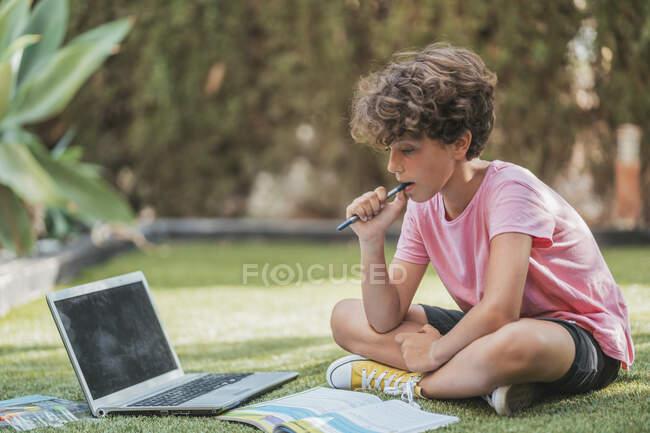 Garçon faisant des devoirs dans le jardin avec ordinateur portable et classeur — Photo de stock