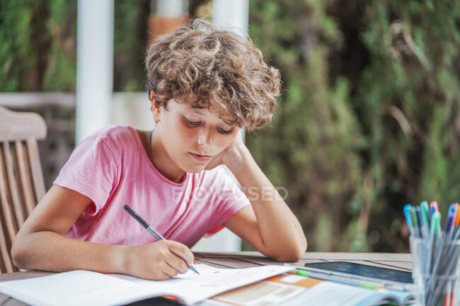 Boy sitting at garden table doing homework — Stock Photo